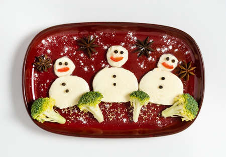 Funny plate with three snowmen made of mozarella cheese and broccoli. Breakfast idea for kids. Vegetarian food for New Year or Christmas celebration. Winter theme food art, top view