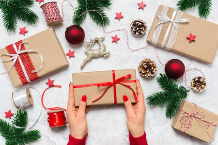Female hands hold Christmas present. Festive holiday composition with woman hands, red nails, gift boxes, pine tree, cones and baubles on marble background. Holiday preparation. Top view, flat lay.