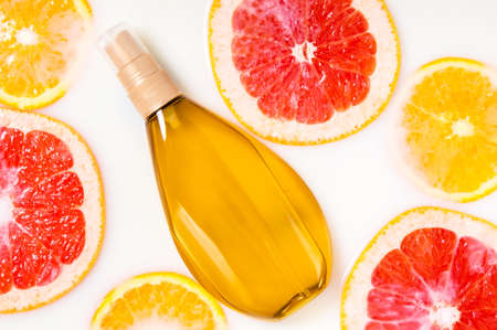 Oil or gel bottle mockup in milk water with grapefruit and orange slices. Organic citrus cosmetics. Beauty spa, vitamin wellness treatment. Fruit skin care cosmetic products for freshness and youth