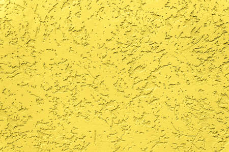 Concrete wall in trendy illuminating yellow color of the year 2021. Textured background. Abstract backdrop with rough stylized texture and copy space for text.