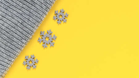 Grey knitted wool texture of sweater, scarf or knit cap and snowflakes in trendy colors of year 2021 illuminating yellow and ultimate gray. Fashionable warm autumn and winter clothes and accessories