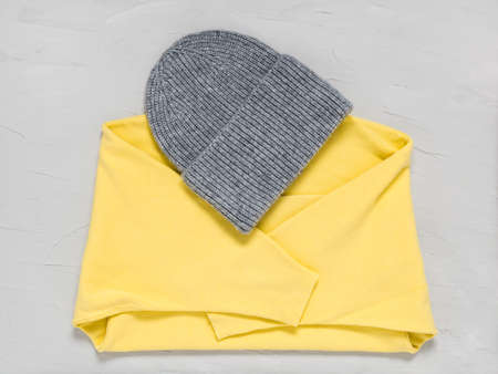 Knitted grey hat and sweater in trendy colors of year 2021 illuminating yellow and ultimate gray. Fashionable warm autumn and winter clothes and accessories. Wool texture on concrete background Фото со стока
