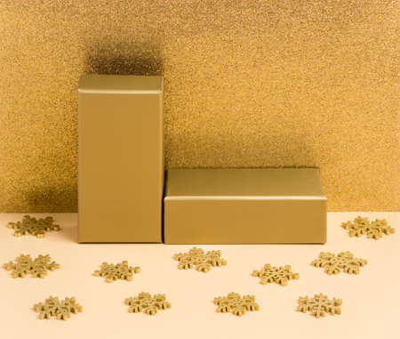 Abstract golden background with podium and snowflakes for product presentation on beige and glitter gold background. Festive holiday mock up for package placement, promotion sale or cosmetic display