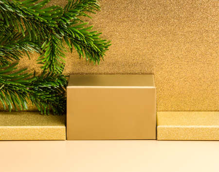 Golden podium for product presentation on beige and luxury glitter gold background, fir tree branch. Winter festive holiday design or mock up for package placement, promotion sale, cosmetic display