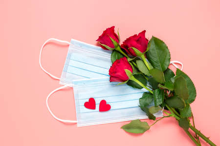 Red roses and disposable face masks with two hearts on pink background. Mothers, womens or Valentines day celebration during coronavirus pandemic. New normal, dating, love and Covid-19 concept