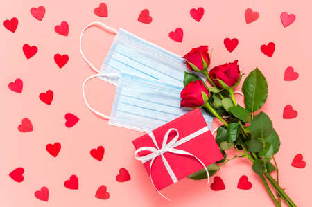 Red roses, gift box and face masks on pink background with many wooden hearts. Mothers, womens or Valentines day celebration during coronavirus pandemic. New normal, dating, love and Covid-19 concept