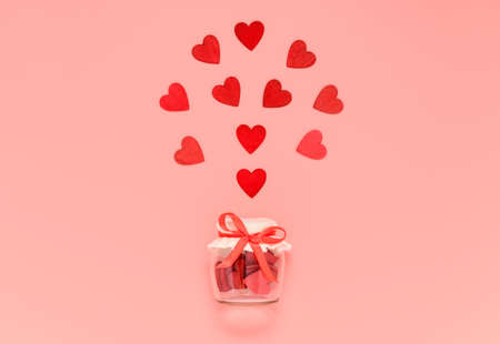 Red wooden hearts in jar with bow knot on pink pastel background. Romantic heart composition for Valentines day or mothers day card. Give and preserve love concept.
