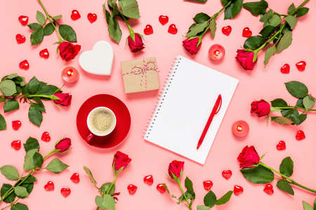 Writing prompts for Valentine's day. Flat lay with red roses, coffee cup, present, hearts and blank notebook on pink background. Be my Valentine. Love and dating concept. Copy space for text Фото со стока