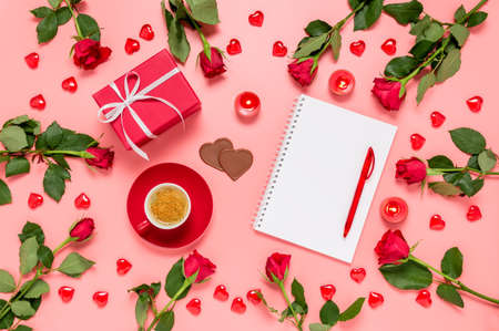 Writing prompts for Valentine's day. Flat lay with red roses, coffee cup, present, chocolate hearts and blank notebook on pink background. Be my Valentine. Love and dating concept. Copy space for text