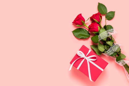 Bouquet of three red roses and gift box on pink background. Birthday, Mother's, women's or Valentine's day greeting. Love and dating concept. Flat lay with copy space for text on left side