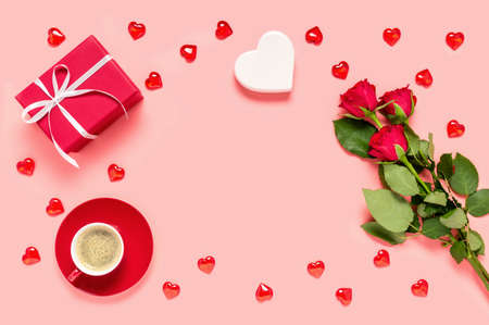 Red roses bouquet, gift box, coffee cup and hearts on pink background. Mother's, women's or Valentine's day celebration. Love and dating concept. Flat lay with copy space for text