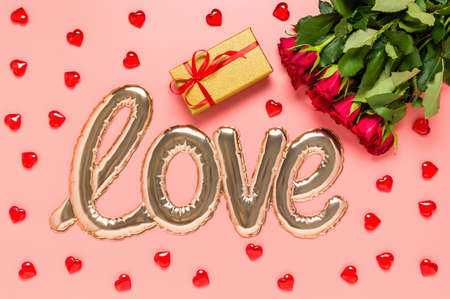Love word shaped with shiny foil balloon, red roses bouquet, golden gift box and wooden hearts on pink background. Mothers, womens or Valentines day. Love and dating concept. Top view, flat lay