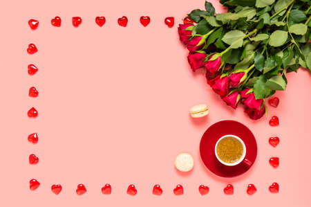 Red roses bouquet, coffee cup and macaroons with frame made of wooden hearts on pink background. Mothers, womens or Valentines day greeting. Love and dating concept. Flat lay with copy space for text Фото со стока