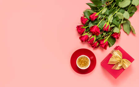 Red roses bouquet, gift box with golden bow knot and coffee cup on pink background. Birthday, mothers, womens or Valentines day celebration. Love and dating concept. Flat lay with copy space for text