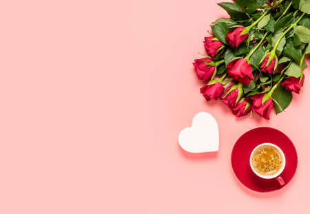 Red roses bouquet, white heart and cup of coffee on pink background. Birthday, mothers, women's or Valentines day celebration. Love and dating concept. Flat lay with copy space for text