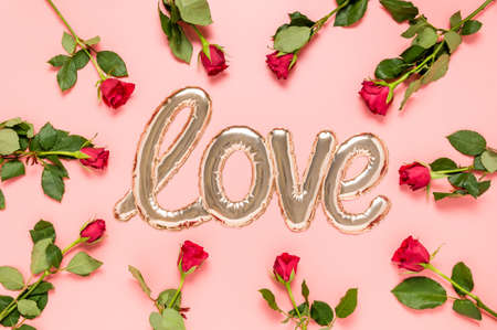 Love word made with shiny shaped golden foil balloon surrounded with red roses on pink background. Mothers, Valentines day or wedding celebration. Top view, flat lay