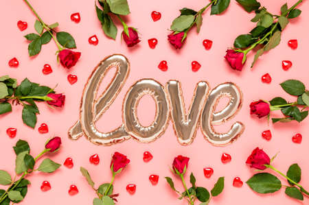 Love word made with shiny shaped golden foil balloon surrounded with red roses and hearts on pink background. Mother's, women's, Valentine's day or wedding celebration. Top view, flat lay