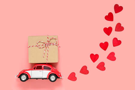 Fulda, Germany - DEC 18, 2020: Small red retro toy car delivering gift box for Valentine's day on pink background with many red hearts. Love and holiday theme. Birthday or Valentines day greeting card Редакционное