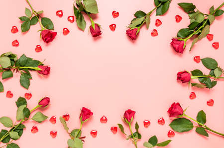 Pink Valentines day with red roses and hearts and copy space in the middle. Фото со стока