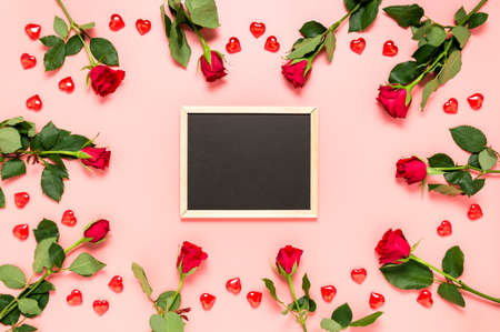 Blank blackboard surrounded with red roses and hearts on pink