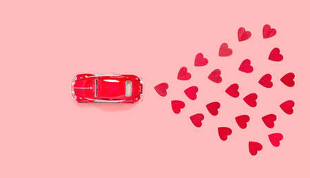 Fulda, Germany - DEC 18, 2020: Red retro toy car with many red hearts for Valentines day on pink background from above. Love and holiday theme, top view. Birthday and Valentine's day greeting card