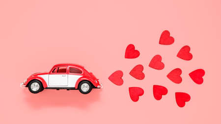 Fulda, Germany - DEC 18, 2020: Small retro toy car with many red hearts for Valentines day on pink background. Love and holiday theme. Birthday and Valentine's day greeting card