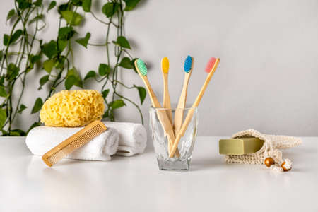 Eco-friendly bathroom accessories: bamboo toothbrush, natural sea sponge, soap in organic saver bag and wooden combo on white table, green plant. Zero waste spa and bath products. Natural skin care