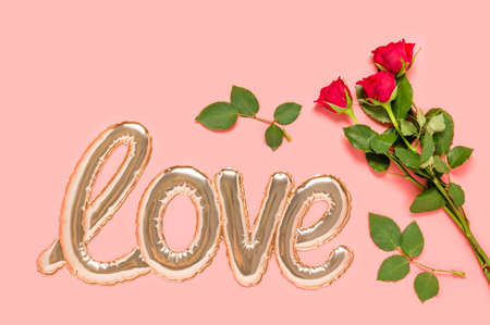Golden foil balloon in shape of Love word and three red roses bouquet on pink background. Love and dating concept. Mothers, Valentines day or wedding celebration. Top view, flat lay