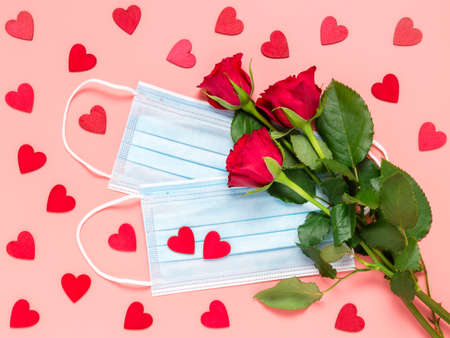 Red roses and disposable medical face mask with many red hearts on pink background. Mothers, womens or Valentines day celebration in pandemic. New normal, dating, love and Covid-19 concept