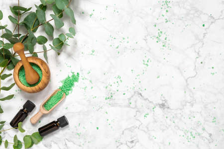 Natural aromatherapy with eucalyptus essential oil bottles and aromatic bath salts on marble background. Organic skin care products. Spa, wellness and relaxation concept. Top view, copy space for text