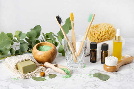 Eco-friendly bathroom accessories: bamboo toothbrush, sea sponge, natural soap in organic saver bag and eucalyptus oil and bath salt. Zero waste spa and organic skin care products 写真素材