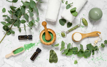 Natural skin care and aromatherapy with eucalyptus essential oil bottles, bath salt, beauty jade roller, gua sha on marble background. Spa, wellness, massage and relaxation concept. Top view, flat lay