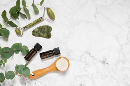 Natural skin care, spa and wellness tools: beauty jade roller, gua sha stone, essential oil and wooden face brush with eucalyptus branch on marble background. Facial massage. Top view and copy space