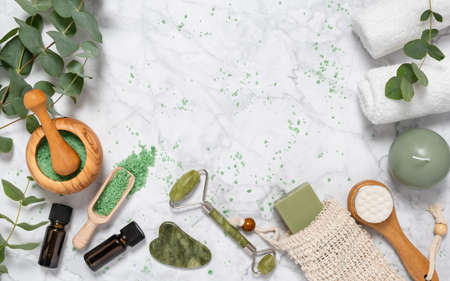 Natural skin care and aromatherapy with eucalyptus essential oil bottle, bath salt, beauty jade roller, gua sha on marble background. Spa, wellness, massage, relaxation concept. Top view, copy space