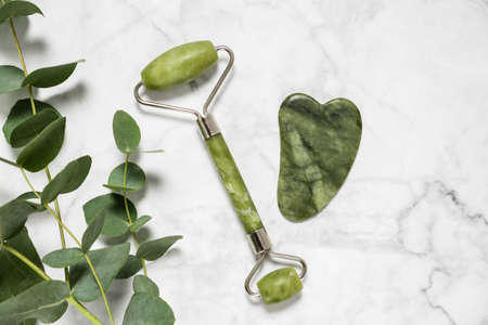 Green jade roller and gua sha stone for facial massage and eucalyptus branch on marble background. Home beauty and selfcare accessories. Face roller for anti age wrinkle treatment. Top view, flat lay. 写真素材