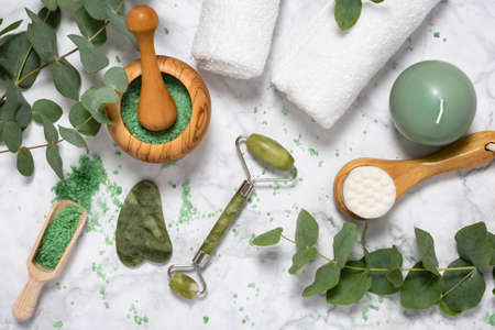 Natural wellness and anti aging skin care with beauty jade roller, gua sha , bath salt and eucalyptus branch on marble background. Spa, face massage, relaxation concept. Top view, flat lay