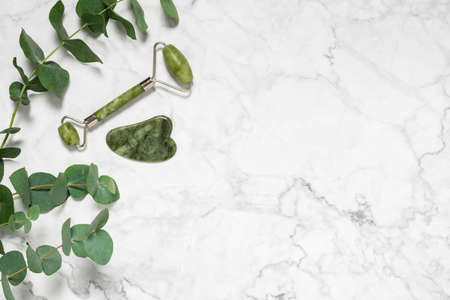 Green jade roller and gua sha stone for facial massage and eucalyptus branch on marble background. Home beauty selfcare accessories. Face roller for anti age wrinkle treatment. Top view, copy space 写真素材