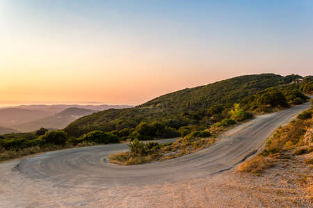 Winding mountain road curve on Corfu island in Greece at sunset. Beautiful landscape view of hills and mountains with lush vegetation over sea 写真素材