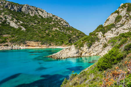 Porto Timoni beach on Corfu island in Greece. Beautiful view of green mountains, clear sea water, secluded Pirates bay and hidden stony beach. Famous destination for summer vacation and hiking