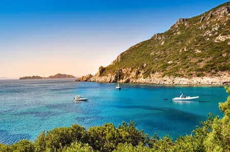 Boats in bay near Porto Timoni beach on Corfu island in Greece. Beautiful view of greek coast with green mountains, clear sea water and Pirate bay. Famous destination for summer vacation 写真素材