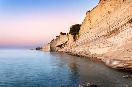 Logas sunset beach with sheer white cliffs in Peroulades village on Corfu Island in Greece. Loggas is famous for scenic viewpoint with sunset sea view from high rocky limestone cliff 写真素材
