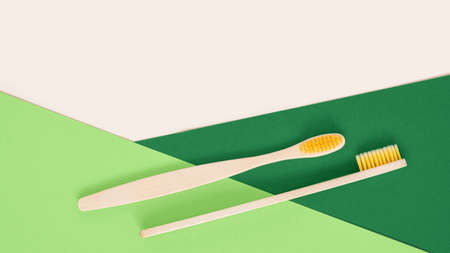 Eco-friendly bamboo toothbrush on geometrical beige and green background. Two natural wooden toothbrushes as plastic free dental care product. Zero waste, sustainable lifestyle. Flat lay, top view