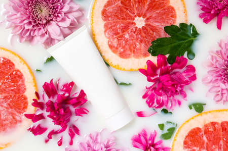 White hand cream tube in milk bath with pink flowers and grapefruit slices. Organic floral or citrus skincare cosmetics. Spa and wellness treatment. Seasonal beauty product. Freshness, youth concept 写真素材