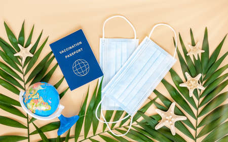 Vaccination or immunity passport, medical mask, globe, sea stars and palm leaves on neutral beige background. Travel and holiday flight restrictions due to global coronavirus or Covid-19 pandemic