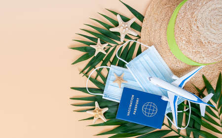 Vaccination or immunity passport, medical mask, airplane, hat, sea stars and palm leaves on neutral beige background. Travel, holiday flight restrictions due to global coronavirus or Covid-19 pandemic