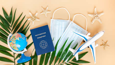 Vaccination or immunity passport, medical mask, airplane, globe and palm leaves on neutral beige background. Travel and holiday flight restrictions due to global coronavirus or Covid-19 pandemic