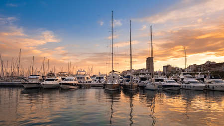 Alicante port with yachts and sailboats at sunset, Spain. Beautiful view of harbor in a touristic town in Costa Blanca region on Mediterranean sea coast