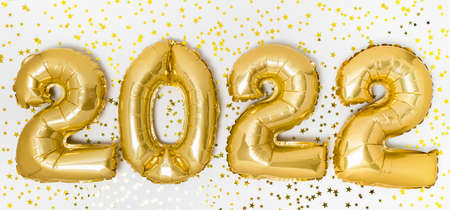 Golden 2022 balloons. Gold metallic foil numbers for Happy New Year celebration on white background with confetti stars