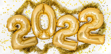 Golden 2022 balloons. Gold metallic foil numbers for Happy New Year celebration on white background with confetti stars and garland