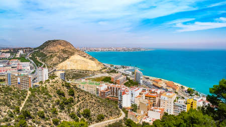 Alicante town with Postiguet beach, Mediterranean sea, Serra Grossa mountain and Cabo de la Huerta district with high buildings, roads. Costa Blanca region in Spain from above